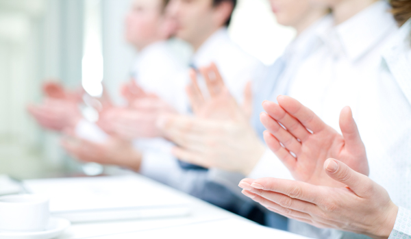 Hands of people clapping at a conference.