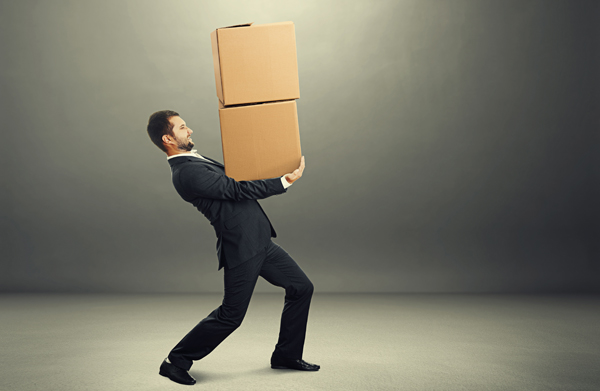 businessman carrying two heavy boxes over grey background