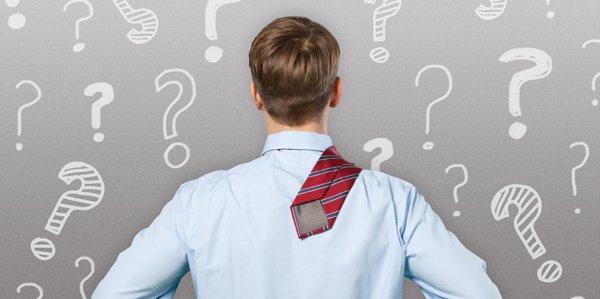 a man standing facing a wall with question marks