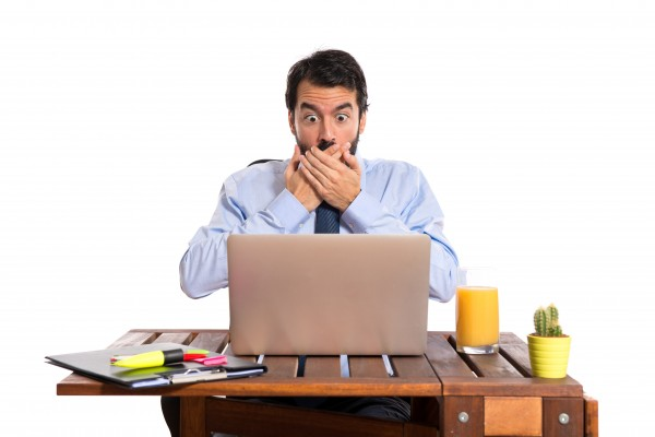 Businessman in front of his computer looking shocked