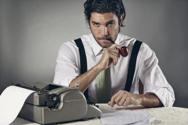 Serious copywriter smoking a pipe in front of a typewriter